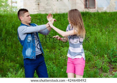 holidays, vacation, love and friendship concept - smiling teen couple young cheerful hipster Best Friends boy and girl having fun, played outdoors, mimic fight, positive emotions, facial expressions - stock photo