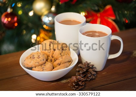 holidays, winter, food and drinks concept - close up of oatmeal cookies, cups with hot chocolate or cocoa drink and pinecones on wooden table over christmas tree background - stock photo