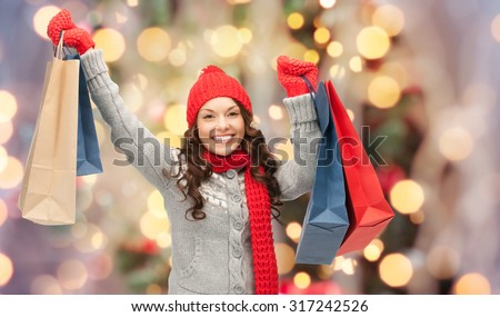 holidays, x-mas, sale and people concept - happy young asian woman in winter clothes with shopping bags over christmas tree lights background - stock photo