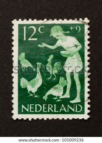 HOLLAND - CIRCA 1950: Stamp printed in the Netherlands shows a child feeding chickens, circa 1950