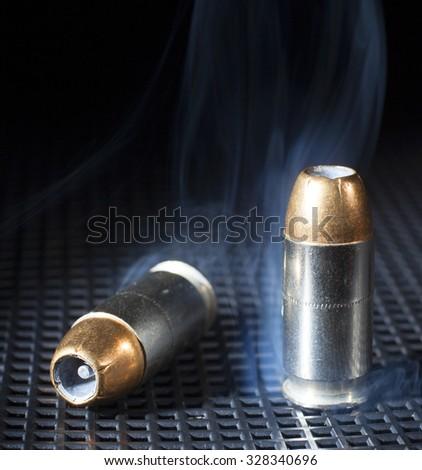 Hollow point bullets on handgun ammo with smoke - stock photo