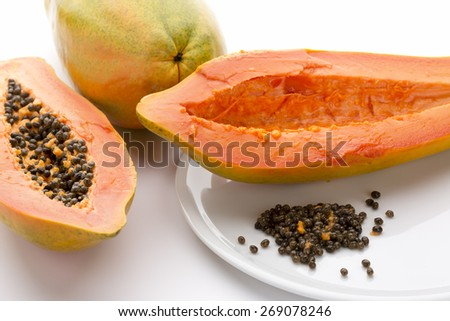 Hollowed out half of a raw papaya in longitudinal cross section and its countless peppery seeds on a white plate. Succulent breakfast fruit of the tropical Carica papaya. Close up. White background. - stock photo