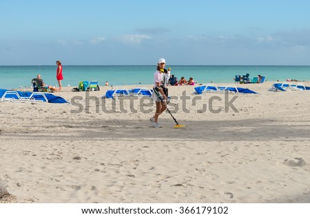 HOLLYWOOD BEACH, FLORIDA - JANUARY 17: An unidentified woman searching with a metal detector for treasures on the beach, photographed on January 17, 2016 - stock photo