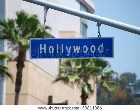 Hollywood Blvd sign with palm tree backdrop. - stock photo