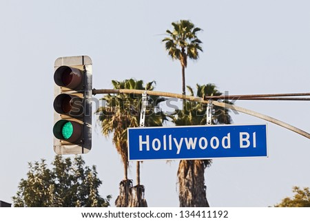 Hollywood Boulevard Sign with Palm Trees and Traffic Signal Light