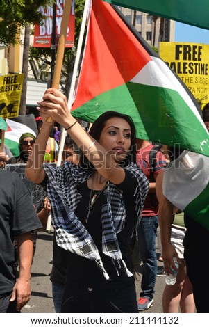 HOLLYWOOD, CA - AUGUST 16, 2014: A Palestinian activist marches along Hollywood Boulevard carrying a Palestinian flag in protest of Israeli military actions in Gaza on August 16, 2014. - stock photo