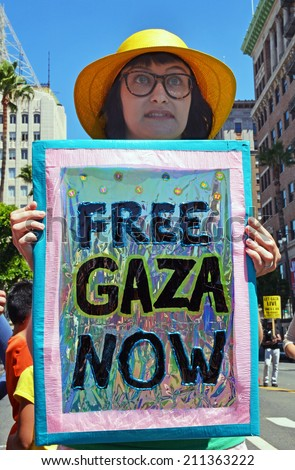 "HOLLYWOOD, CA - AUGUST 16, 2014: A protestor on Hollywood Boulevard holds a sign which reads, ""Free Gaza Now"" protesting Israeli military actions in Gaza on August 16, 2014 in Hollywood, California."