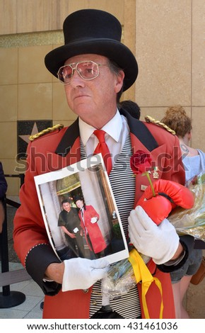HOLLYWOOD, CA - JUNE 4, 2016: A Hollywood Ambassador in a red uniform  holds various tributes to Muhammad Ali near his star on public display on the Hollywood Walk of Fame on June 4, 2016.
