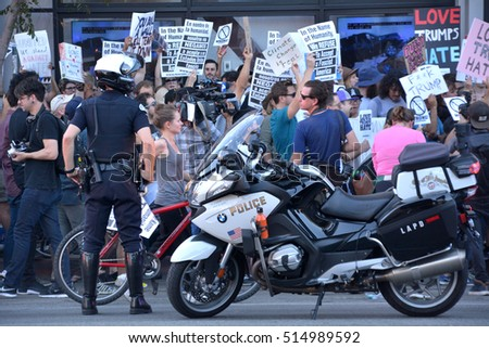 HOLLYWOOD, CA - NOVEMBER 13 2016: Two police officers stand watch as protesters rally against the election of Donald Trump on November 13, 2016 in Hollywood, California.