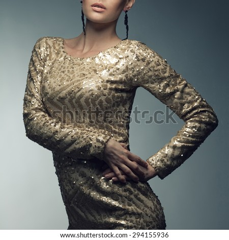 Hollywood movie star, femme fatale concept. Portrait of young beautiful caucasian blonde in gorgeous vintage golden dress with sequins. Luxurious earrings. Perfect evening make-up. Studio shot - stock photo