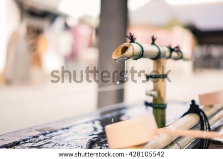 Holy bamboo fountain with dripping water for hands wash in Japanese temple - stock photo
