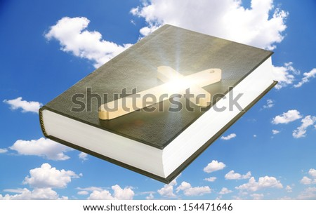 Holy Bible and wooden cross on sky background - stock photo