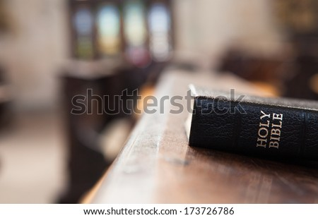 Holy Bible on a wooden church bench. - stock photo