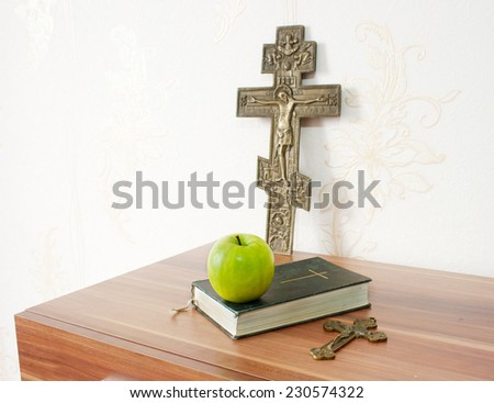 holy bible with green apple and two crosses on the brown wooden table - stock photo