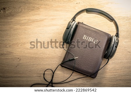 Holy Bible with headphones - symbol of listening to the Word of God.