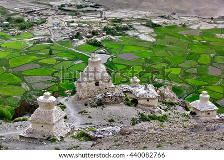 Holy Place, the ancient Buddhist white stupa on the hill above the green fields and a small village in the valley Padum, Zanskar, Himalayas, Northern India. - stock photo