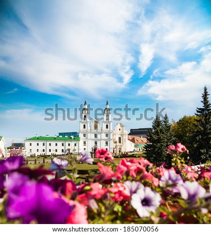 Holy Spirit Cathedral in Minsk, Belarus. View of Orthodox Church and Historical Center (Nemiga). Defocused Flowers on the Foreground. - stock photo