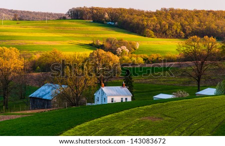 Home and barn on the farm fields and rolling hills of Southern York County, Pennsylvania. - stock photo