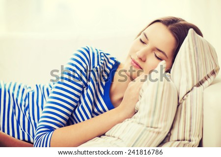 home and happiness concept - smiling teenage girl sleeping on sofa at home - stock photo