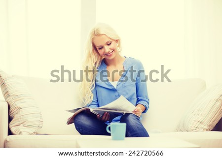 home and leasure concept - smiling woman sitting on couch and reading magazine at home