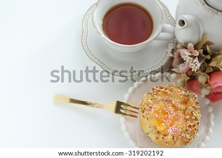 Home bakery orange and candy decoration bun with tea - stock photo