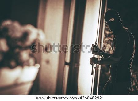 Home Burglar in a Mask Breaking Into the House. House Thief Concept Photo. - stock photo