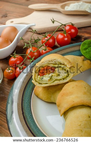 Home calzone rolls stuffed with cherry tomatoes, basil pesto and spinach with bio garlic