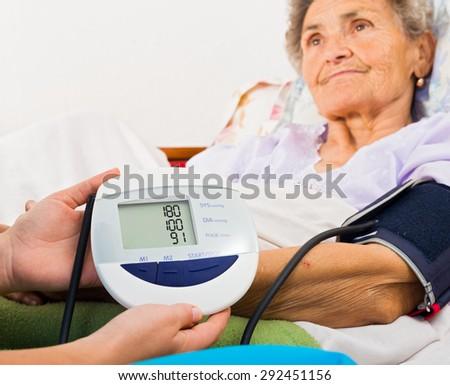 Home care nurse using digital blood pressure measure. - stock photo