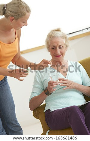 Home-care young girl helping elderly lady to take her medicine.  - stock photo