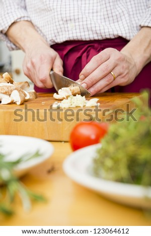 Home chef, cutting mushrooms on a wooden cutting board, with herbs and other ingredients in the foreground