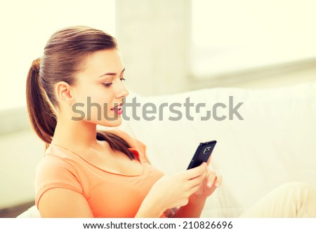 home, communication and internet - woman sitting on the couch with smartphone at home - stock photo