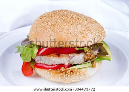 Home cooked burger with turkey, avocado, lettuce, onions, red paprika pepper on a sesame seed bun - stock photo