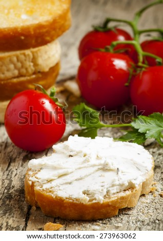 Home crostini with soft cheese and tomatoes on a wooden table, selective focus