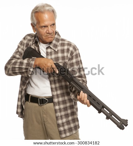 HOME DEFENSE   Mature adult with shotgun or firearm, looking serious. - stock photo