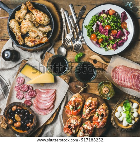 Home dinner, party table arrangement. Rustic table set with salad, olives, chicken, tomato, feta cheese brushettas, snacks and red wine, top view. Slow food, banquet, catering concept, square crop