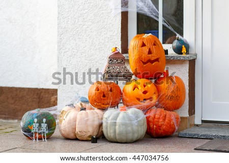 Home door decorated for halloween with scary jack-o-lantern pumpkins, candles, spider webs and skeletons - stock photo