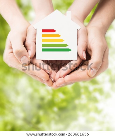 Home. Energy saving, real estate and family home concept - closeup of couple hands holding white paper house with energy efficiency rating - stock photo