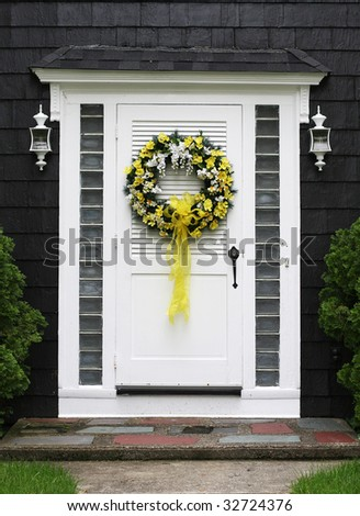 home entrance with decorative wreath on front door - stock photo