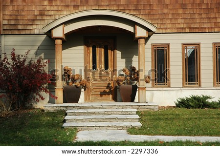 Home entrance with lots of wood trim and wooden door flanked by two planters with hydrangeas - stock photo