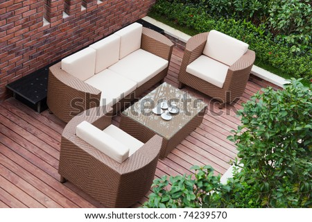 Home exterior patio with wooden decking and rattan sofa view from the top. - stock photo