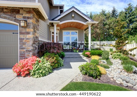 Home exterior with garage and driveway, patio area with nice landscaping desing around - stock photo