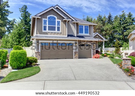 Home exterior with garage and driveway with nice landscaping desing around - stock photo