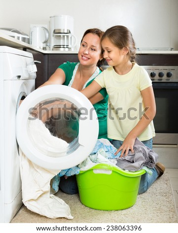 Home family laundry. Happy mother with preschooler daughter loading clothes into washing machine in kitchen. Focus on girl - stock photo