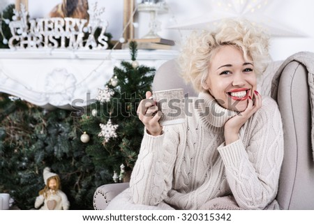 Home festive atmosphere. Drinking tea while sitting in a chair with a knitted plaid by the fireplace. Charming big smile woman. Series of winter holiday photos. - stock photo