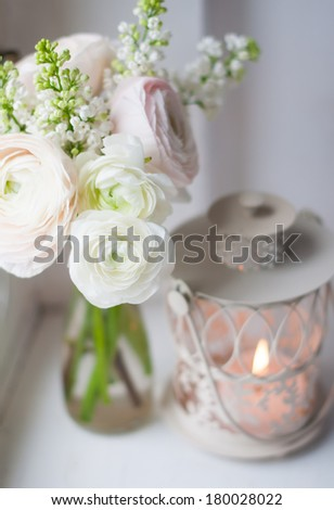 Home festive decorations, elegant bouquet of flowers, buttercups and white lilac and candle lantern on white vintage windowsill