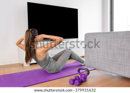 Home fitness concept. Woman doing strength training abs situps bodyweight floor exercises watching a dvd workout or web videos on a smart tv in the living room of a house or apartment. - stock photo