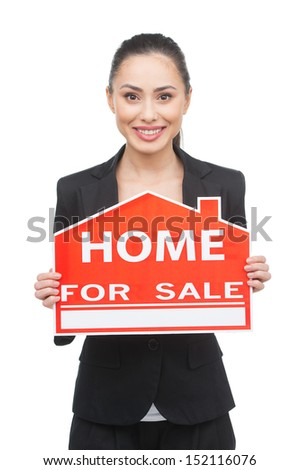 Home for sale. Happy young woman in formalwear holding a home for sale sign while isolated on white