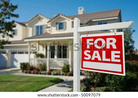 Home For Sale Real Estate Sign in Front of New House. - stock photo