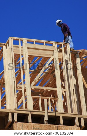 Home frame with construction worker present on structure