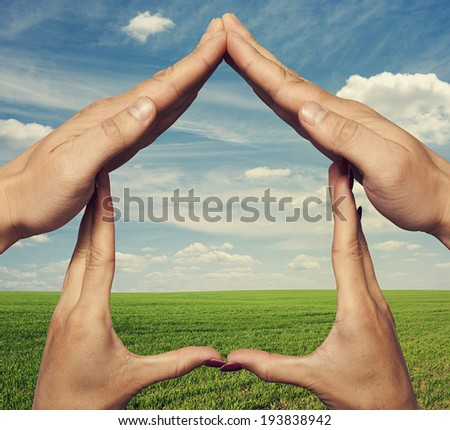 home from hands over green field and blue sky - stock photo